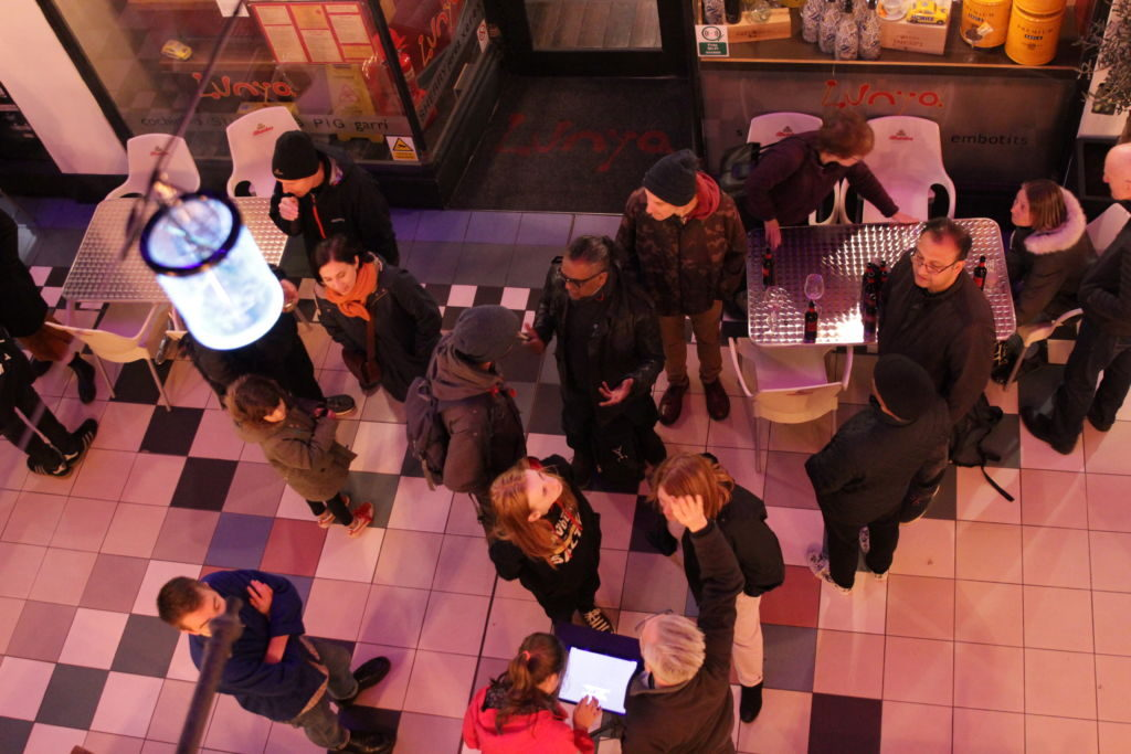 Image of people listing to the Radical Shopper Installation.